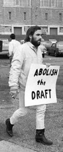 "protestor holding a sign that says ""abolish the draft"""