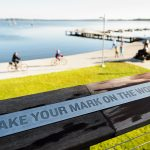 "Sign at Alumni Park that says ""Make your mark on the world"""