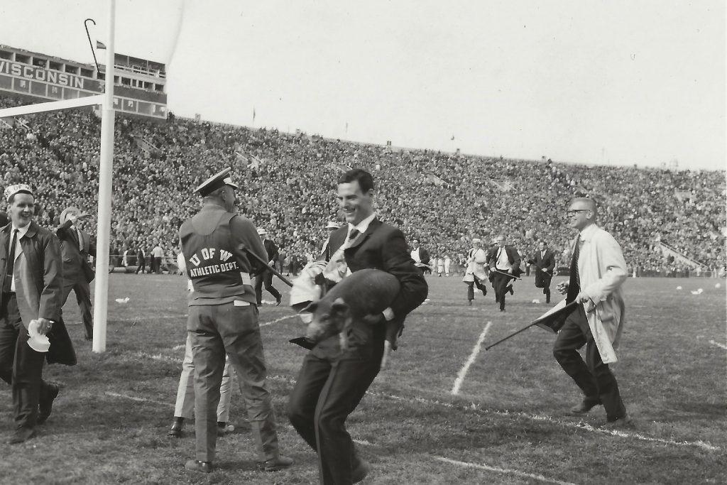 Student James Schernecker at cane toss, holding a pig