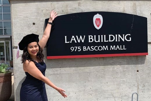 2020 graduate posing with law building