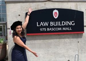 2020 graduate posing with law building sign
